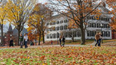 学生们 walk through campus in the fall.